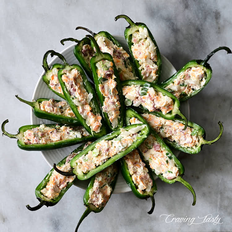 Raw stuffed jalapeno peppers on a plate.