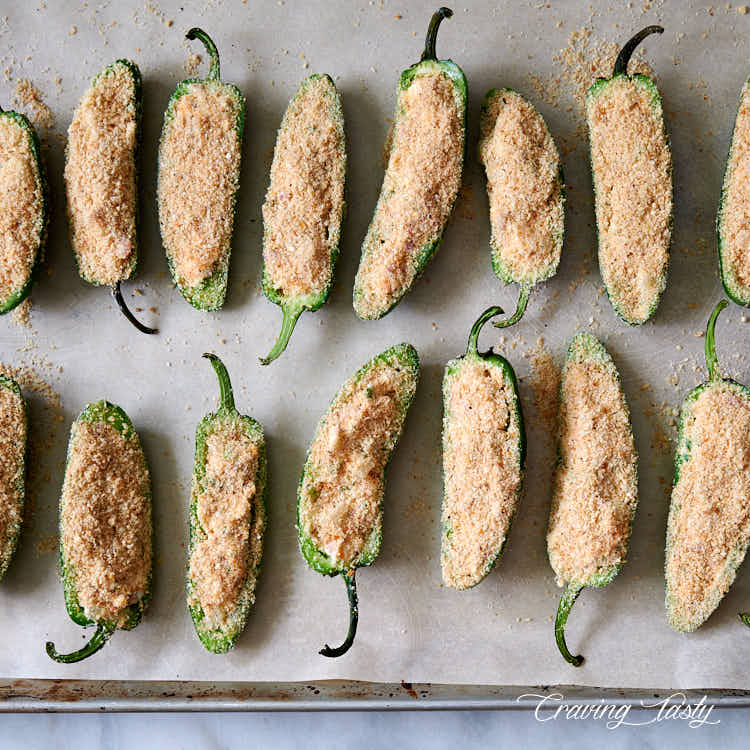 Stuffed jalapeno peppers, dredged in bread crumbs and Parmesan cheese mix, on a baking sheet.