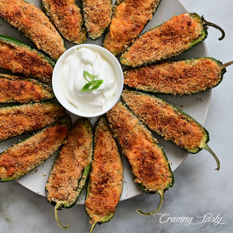 Baked jalapeno poppers on plate with a white dipping sauce.