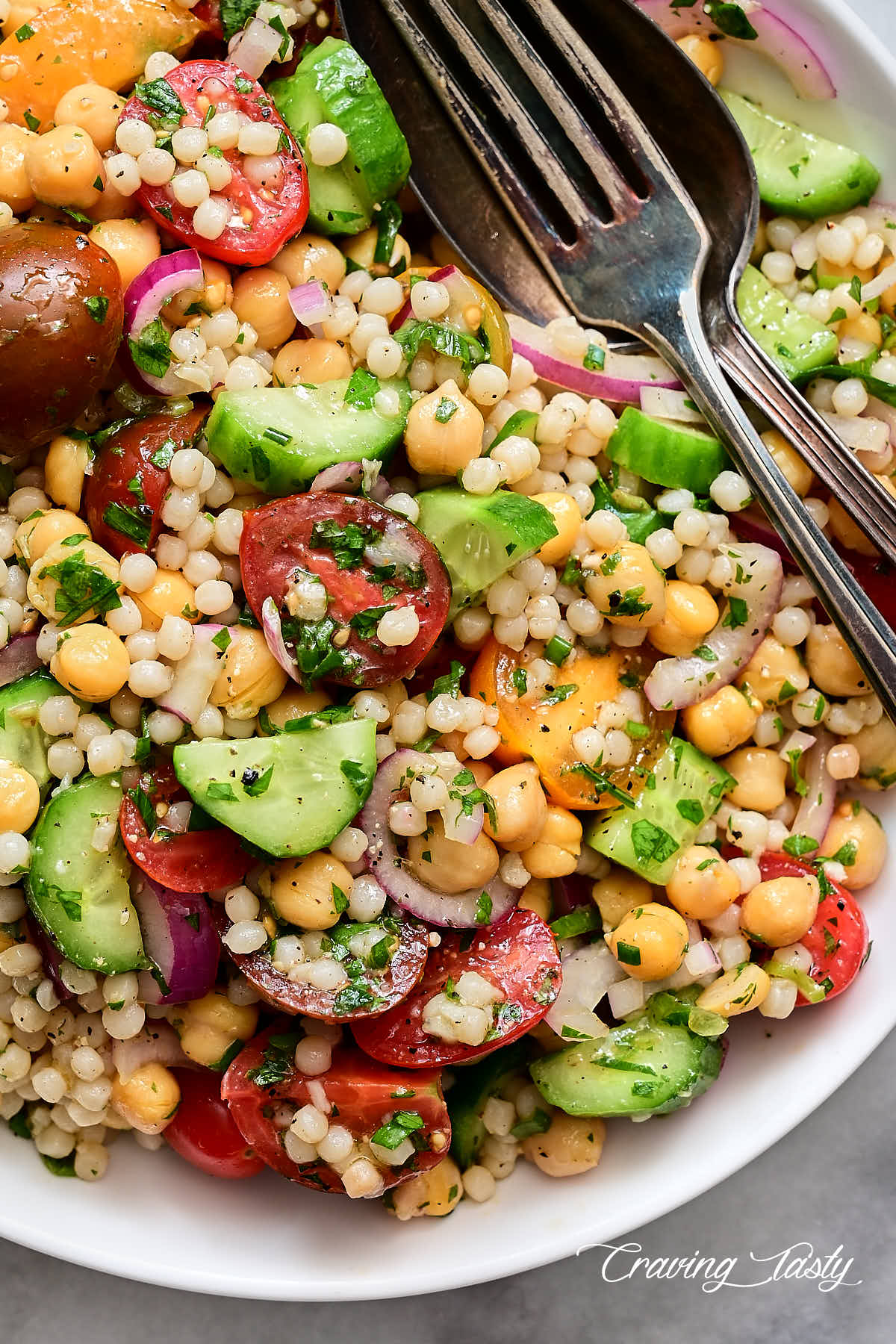 Israeli couscous salad in a white bowl with a fork and a spoon inside.