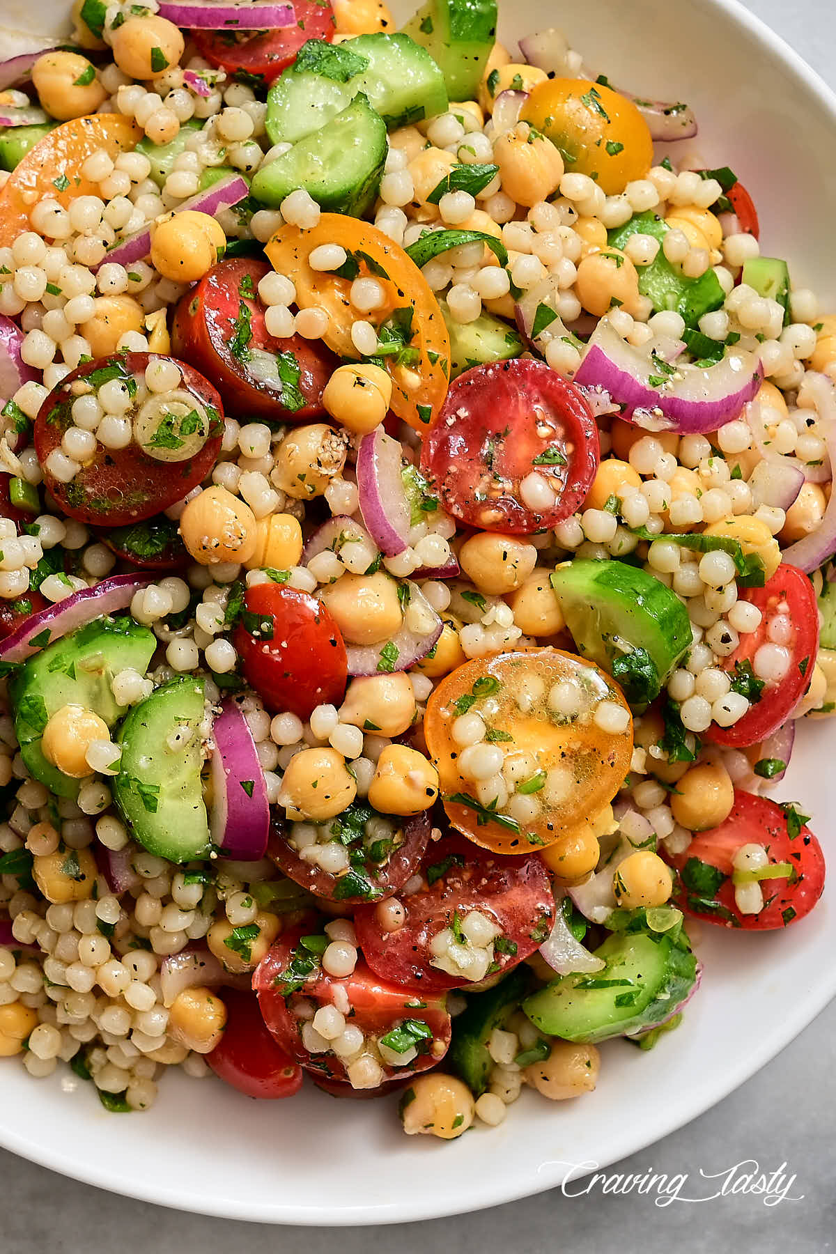 Israeli couscous salad with heirloom tomatoes, cucumbers and herbs on a white plate.