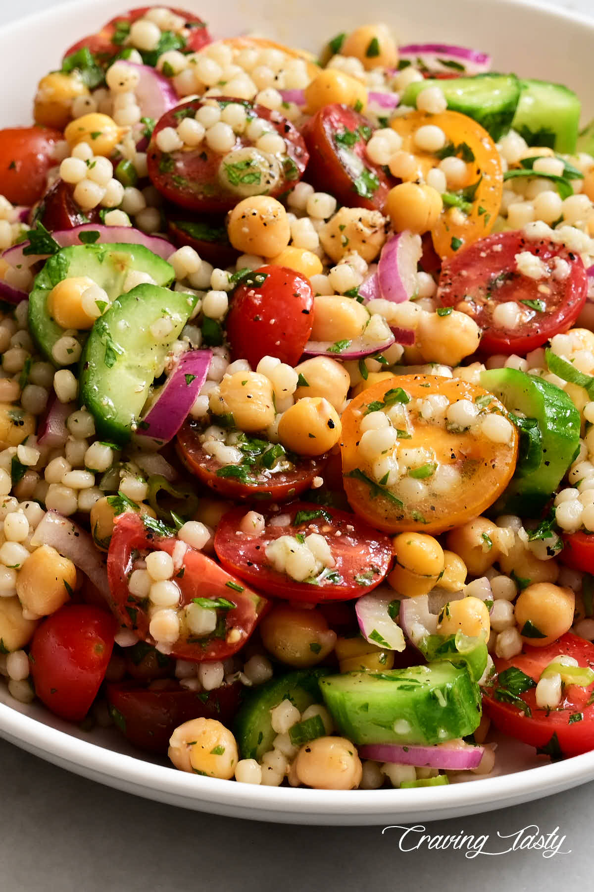 Close up of cherry tomatoes, Israeli couscous, cucumbers, red onion and herbs in a bowl to comprise an Israel couscous salad.