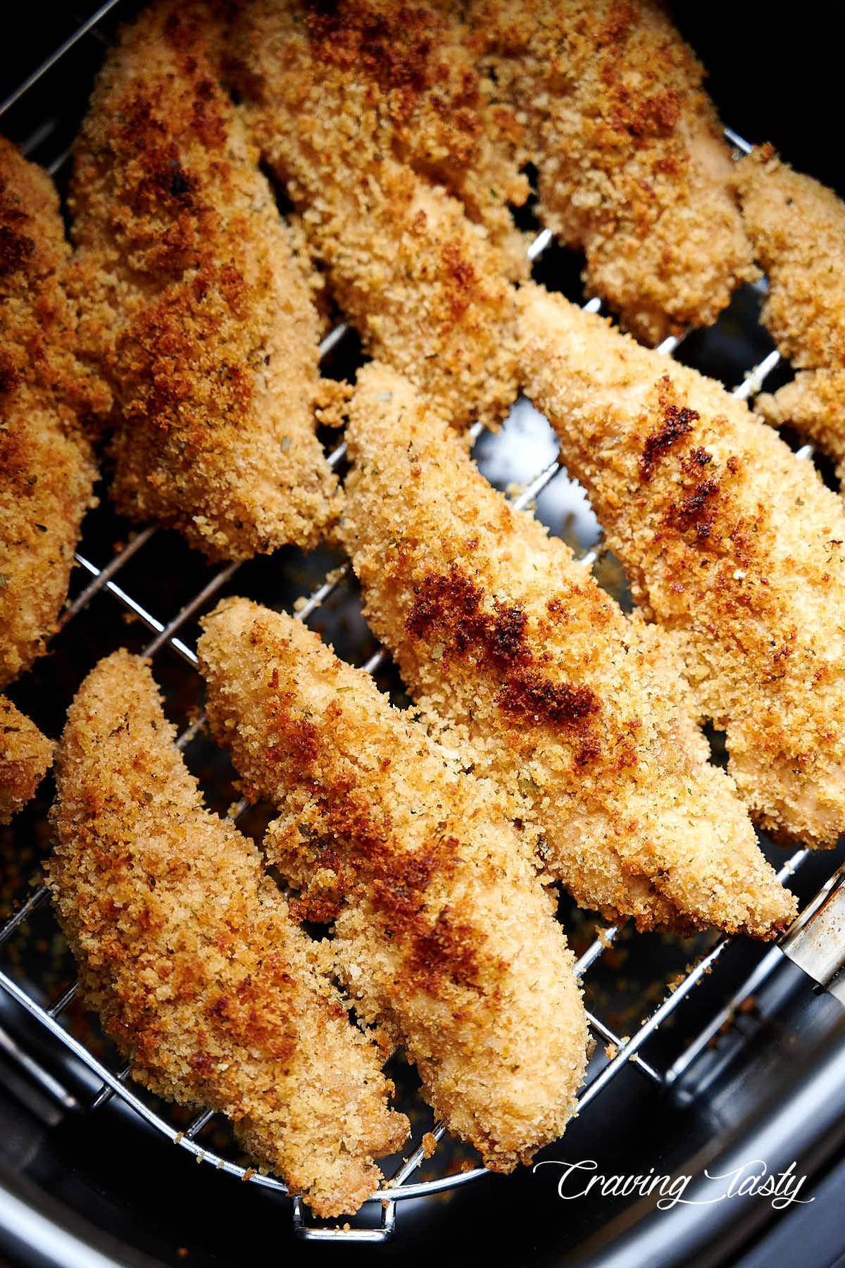 Golden brown chicken tenders inside air fryer.