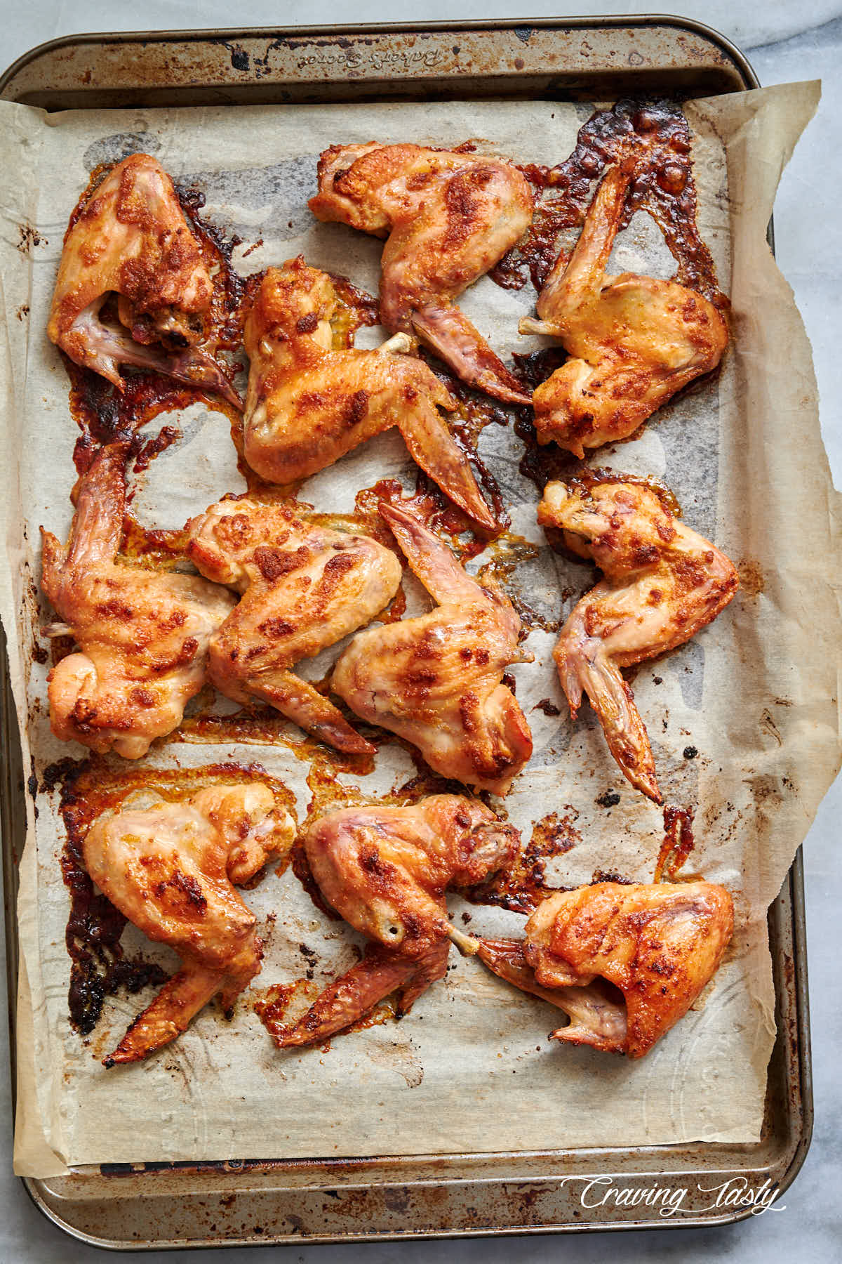 Baked chicken wings, golden brown, on a baking sheet lined with parchment paper.