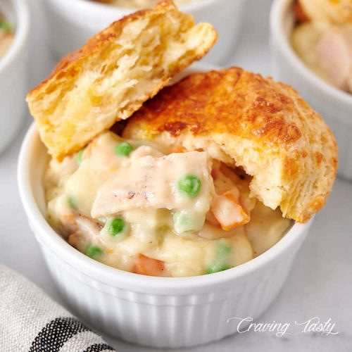 Close up of a bowl of creamy chicken with potatoes, peas and carrots, with biscuit split in half on top.