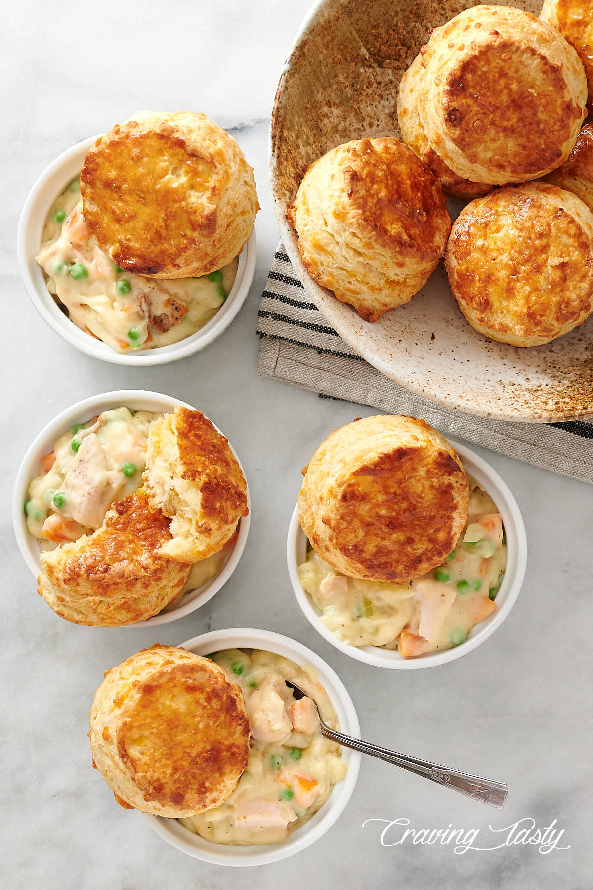 Ramekins filled with creamy chicken, topped with golden brown biscuits.