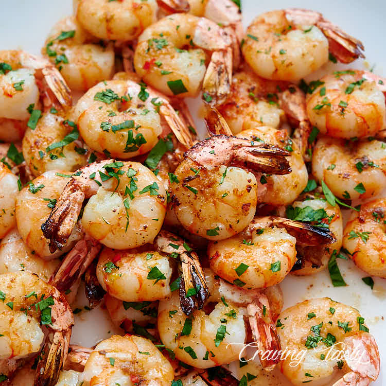 Close up of broiled shrimp on a white serving platter.