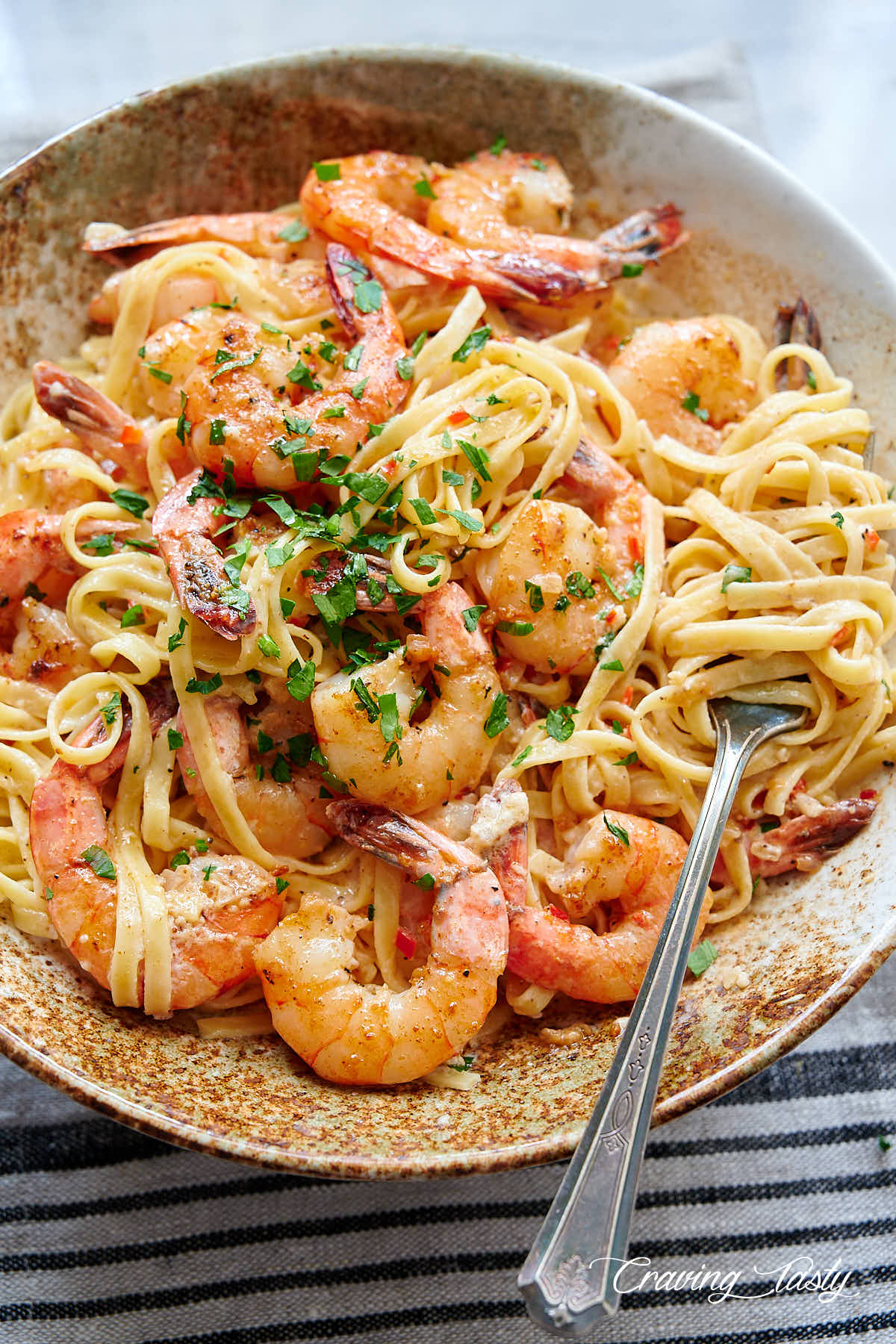 Garlic butter shrimp and pasta in a bowl garnished with parsley.
