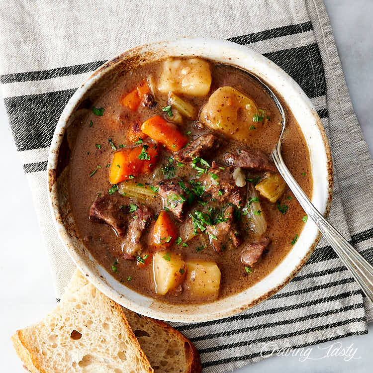 Top down view of a bowl of beef stew, with a spoon and bread on the side.