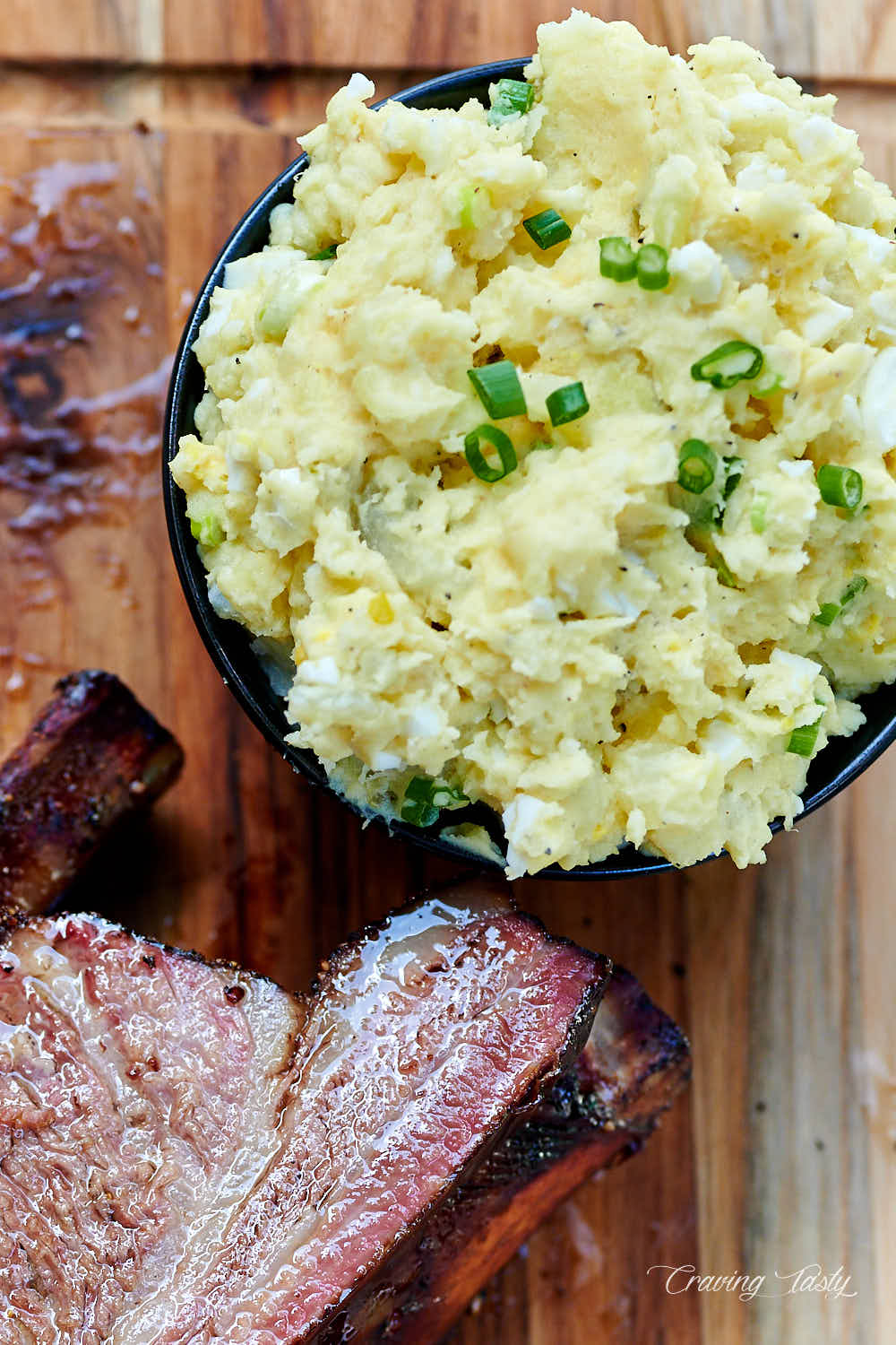 A bowl of southern potato salad next to smoked beef ribs.