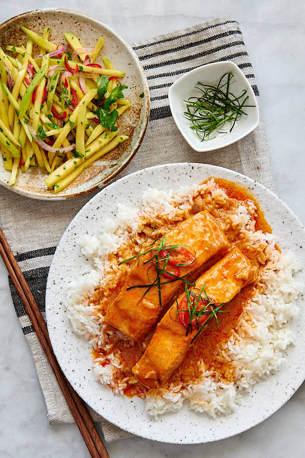 Curry salmon over white rice in a bowl, served with mango salad.