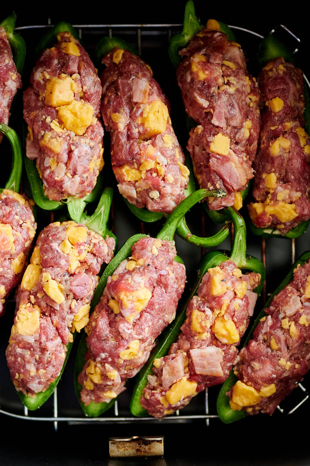 Close up of uncooked stuffed jalapeno poppers inside air fryer