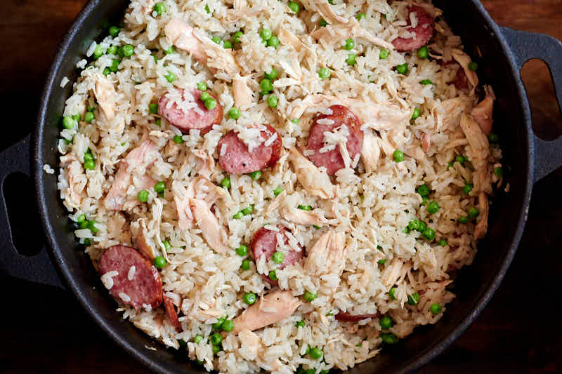 Chicken bog mixed rice, peas, chicken and sausage in a large pot