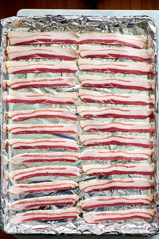 Raw bacon slices on baking sheet