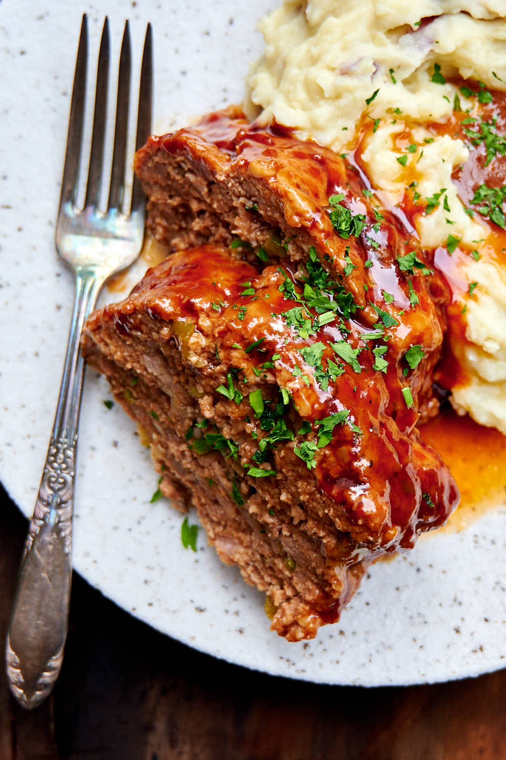 Meat loaf made in Instant Pot on a plate with mashed potatoes and gravy.