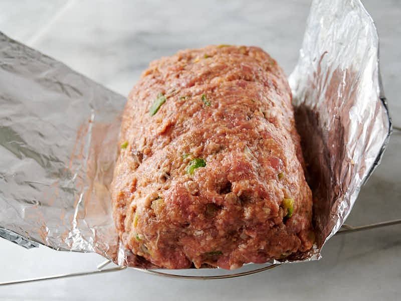 Meatloaf shaped into a long on a aluminum foil sling.