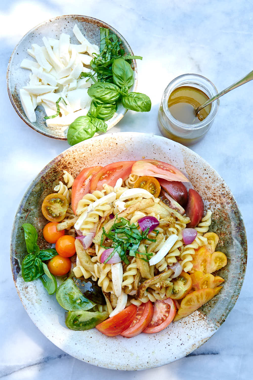 Colorful summer pasta salad with dressing on the side